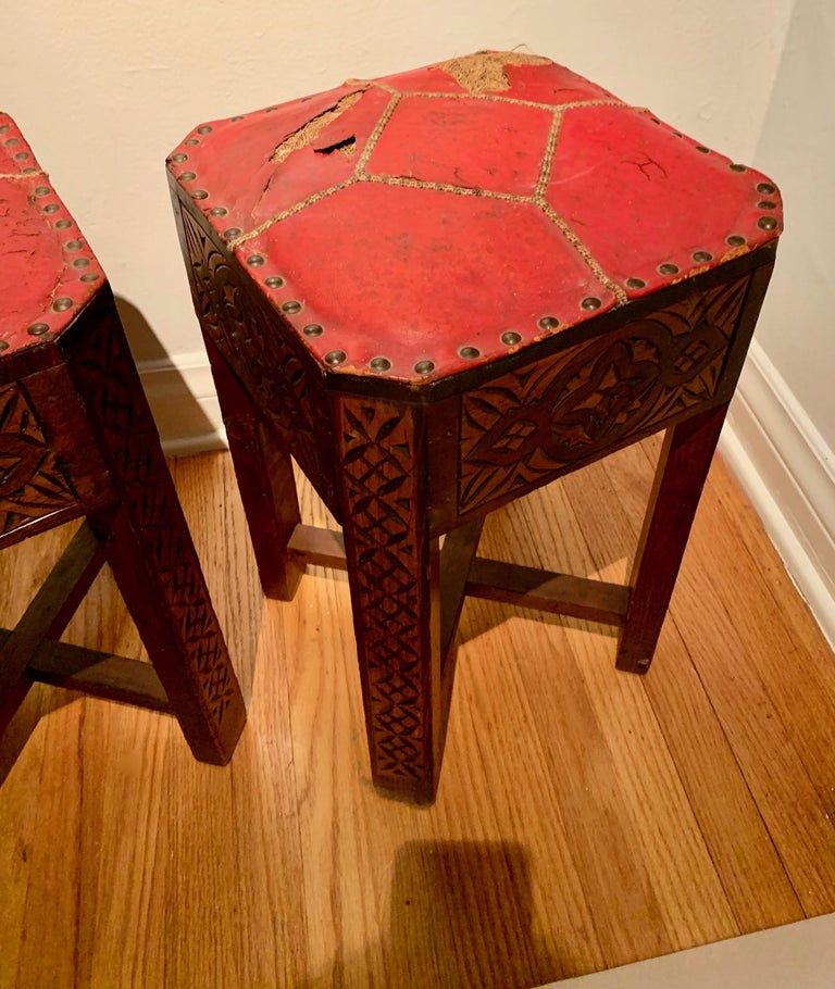 Pair of hand carved Arts & Crafts stools - the unique and rare pair have been kept in the original condition with intricate woven seams. The cracked and patinated red leather has exposed horse hair, suited for the most unique spaces. Well made and