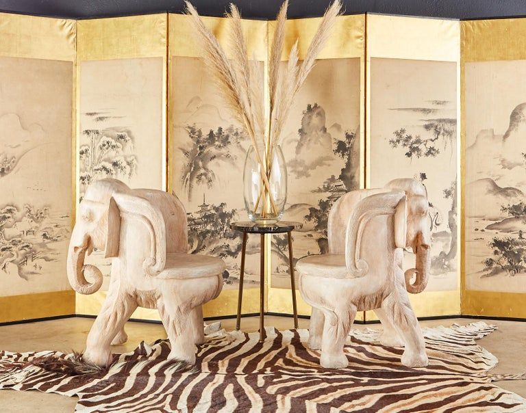 Charming pair of hand carved hardwood elephant chairs crafted from large tree trunks. Beautifully crafted with detailed faces and trunks. Featuring a white-washed or bleached finish that gives them an attractive patina but still showcases the
