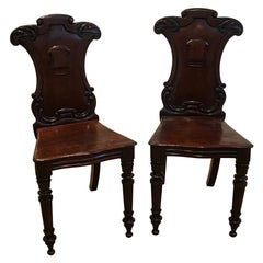 Pair of Hand Carved Mahogany Armorial Hall Chairs
