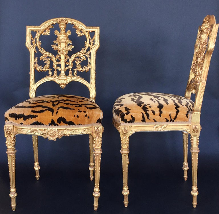Pair of detailed hand carved giltwood chairs with tiger upholstery.