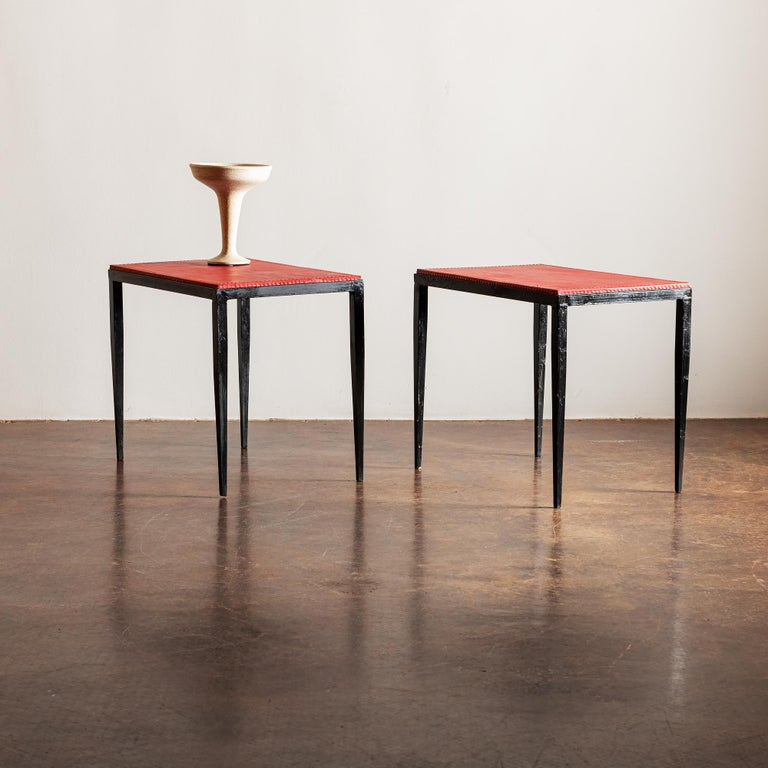 A pair of iron and red leather end tables with contrasting stitching in the manner of Jean-Michel Frank, France, 1940s.