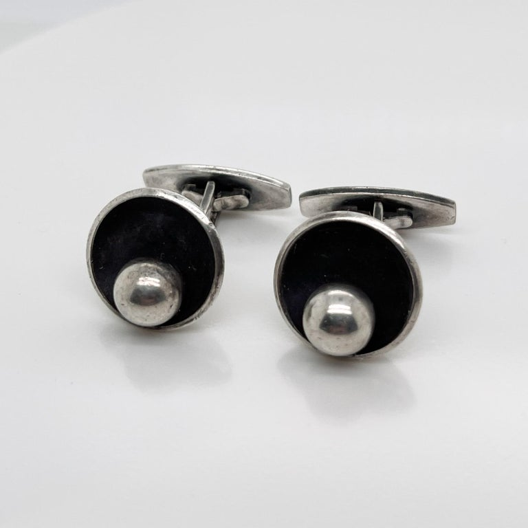 A very fine pair of Hans Hansen Danish Modern sterling silver cufflinks.  Model no. 610.  Each with a round silver ball that is set on the side of a silver bowl form.   Simply terrific cufflinks from one of the Danish Modern masters!  Date: 20th