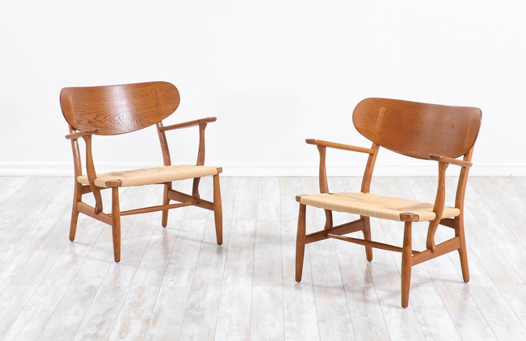 A pair of iconic CH-22 lounge chairs designed by Hans J. Wegner in collaboration with the famous workshop of Carl Hansen & Søn in Denmark during the 1950s. Our chairs feature large molded curbed backrests for optimum comfort that feel as if they hug
