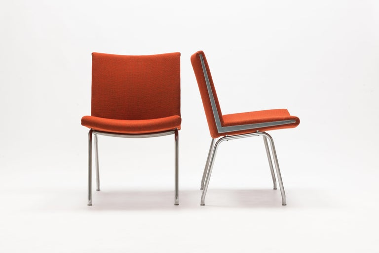 Pair of Hans Wegner AP37 'Airport' Chairs by A.P. Stolen Denmark,  Exceptional modern designed chairs on steel frames with sharp triangle shape chrome details on both sides of each seat.  Seats are upholstered in a red Hallingdal fabric. This is a