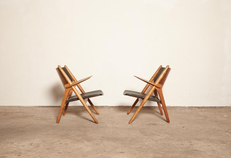 A pair of oak Hans Wegner CH-28 sawbuck armchairs with leather seats. Made by Carl Hansen and Son, Denmark.   With the makers mark of the Carl Hansen craftsman who made the chairs.    Ships worldwide.