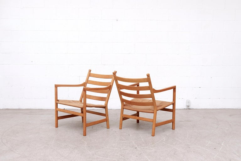 Pair of midcentury 'CH44' lounge chairs from 1965 by Hans J. Wegner for Carl Hansen & Son. Inspired by American shaker furniture, The CH44 lounge chair is made from solid oak and features paper cord woven seating. The frames are in good original