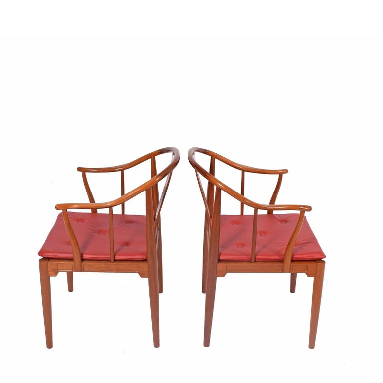 Solid mahogany armchairs with red leather cushions designed by Hans Wegner for Fritz Hansen in 1944. Inspiration came from a 1400 Chinese chair he saw in a museum.