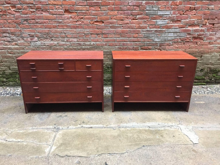 Beautiful pair of cabinets designed by Hans Wegner for Ry Mobler, Denmark. Teak veneer construction with solid teak handles. One cabinet contains six drawers with the two top drawers felt lined. It retains the original brass key, but it has been