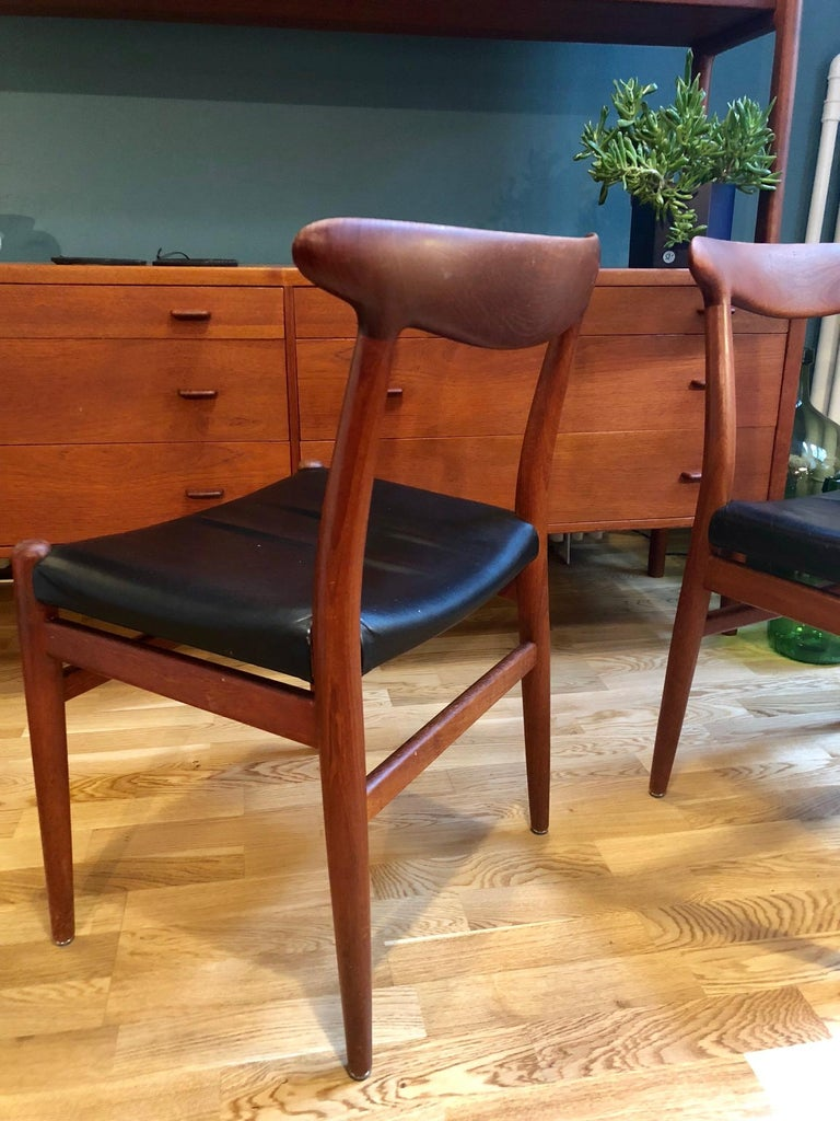 Beautiful, rare set of 2 Hans Wegner chairs made of teak and black leather. Comfortable and well preserved. Model W2 Production by C.M. Madsen Denmark 1953. Beautiful processing of teak. Marked.