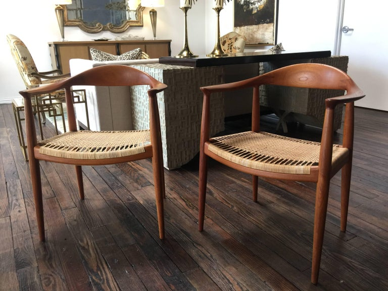 Beautiful pair of round chairs by Hans Wegner. Cane seats. One seat was replaced so a slight variation in color that will disappear over time. Both show very well.