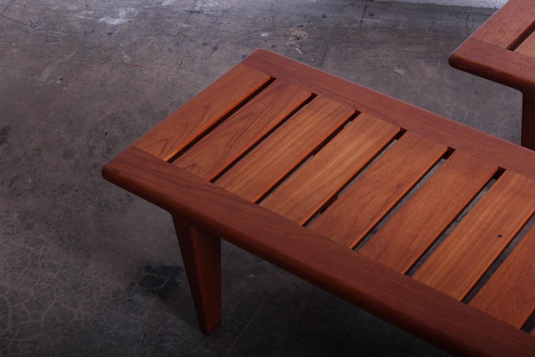 A pair of solid teak benches designed by Hans Wegner for Johannes Hansen.
