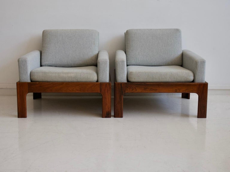 Pair of lounge chairs attributed to Illum Wikkelsø. Made of solid hardwood and upholstered in wool fabric. Produced by Eilersen. Few stains on the upholstery.