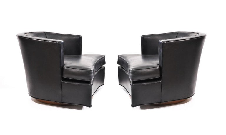Mid-Century Modern comfortable pair of swiveling lounge chairs designed by Harvey Probber, Model 303A. The chairs professionally re-covered in a black leatherette upholstery with decorative nails lining the corners on swivel bases in oakwood.