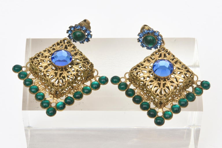These pair of stunning and dramatic vintage signed Hattie Carnegie clip on multi colored jewel toned dangle chandelier earrings are an eye catcher on the ear lobes. These are from the 60's. The open gold filled filigree work adds extra dimension.