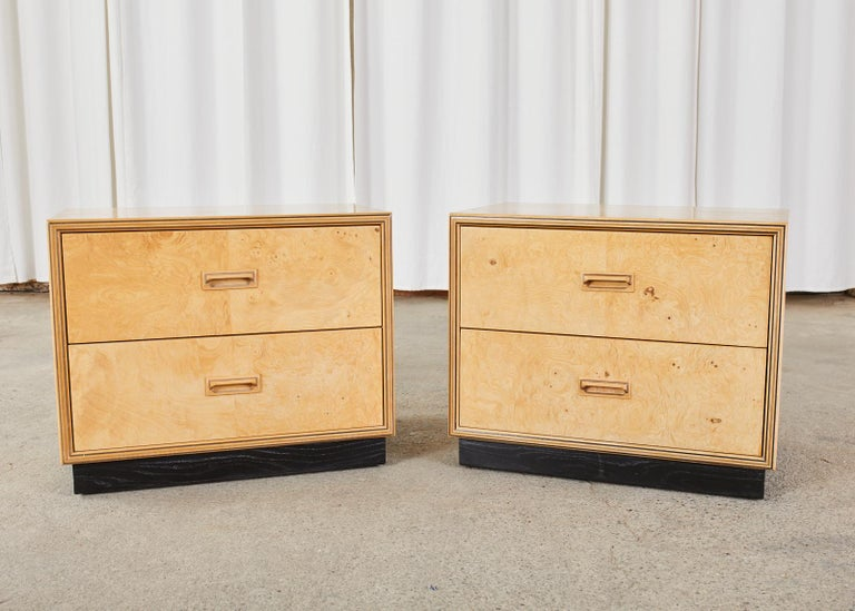 Stunning pair of low bachelors chests or nightstands made by Henredon's Scene Two collection. The chests feature a burl olive wood on the front of the drawers and an ash hardwood case finished in blonde. The nightstands are mounted to an ebonized
