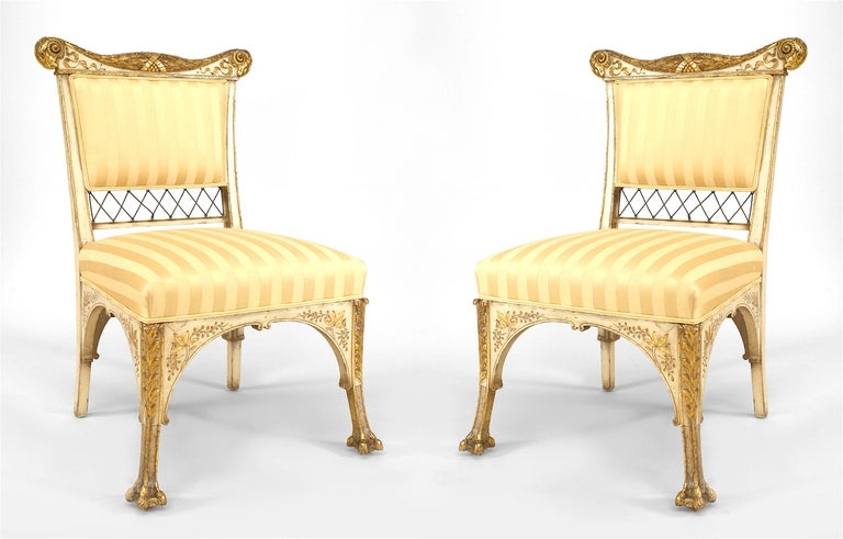 Attributed to famed nineteenth century American furniture designers the Herter Brothers, this pair of white-painted side chairs feature striped upholstery,  carved and gilded backs with lattice bottoms, and intricately carved, clawfooted parcel gilt