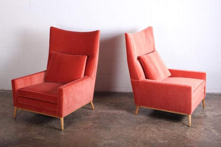 A pair of high back wing chairs designed by Paul McCobb for Winchendon. Newly upholstered in a melon colored velvet with maple legs.