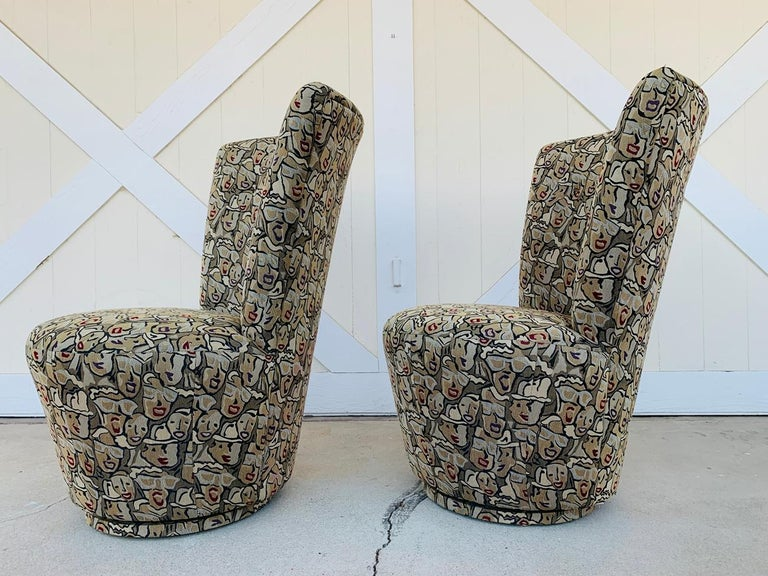 Pair of highback swivel chairs designed and manufactured in the US by Carter Furniture.  The chairs were custom made for James Wilson and custom upholstered, the name of the fabric pattern is Hot Lips Cherry.  The chairs are in very good