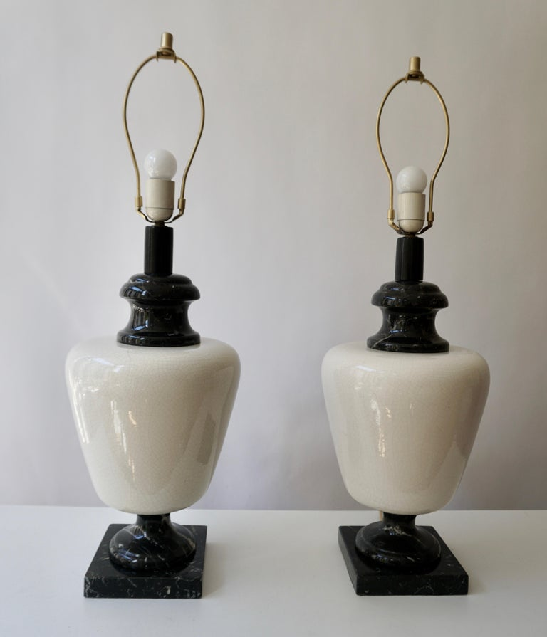 Stunning pair of polished black and white marble table lamps. Both lamps are in very good original and working condition. Priced and offered as a pair, lamps accept standard E27 size screw in bulbs.  Measures: Diameter 47 cm. Height marble base