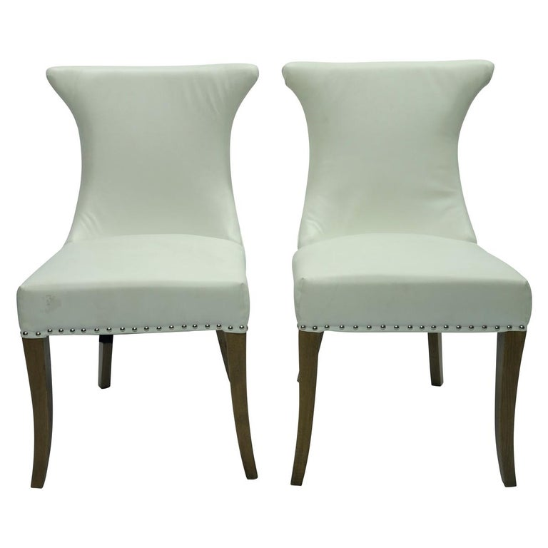 Handsome pair of Hollywood Regency white faux leather rolled back dining chairs.