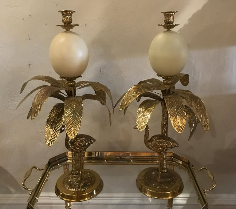 Pair of faux ostrich egg, ostrich & palm tree brass candlesticks in the Hollywood Regency style.