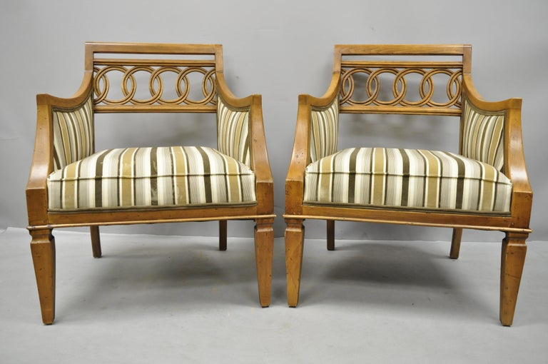 Pair of Hollywood Regency French style carved spiral back armchairs. Items feature striped upholstered seats, carved backs, solid wood construction, beautiful wood grain, distressed finish, tapered legs, sleek sculptural form, circa late 20th