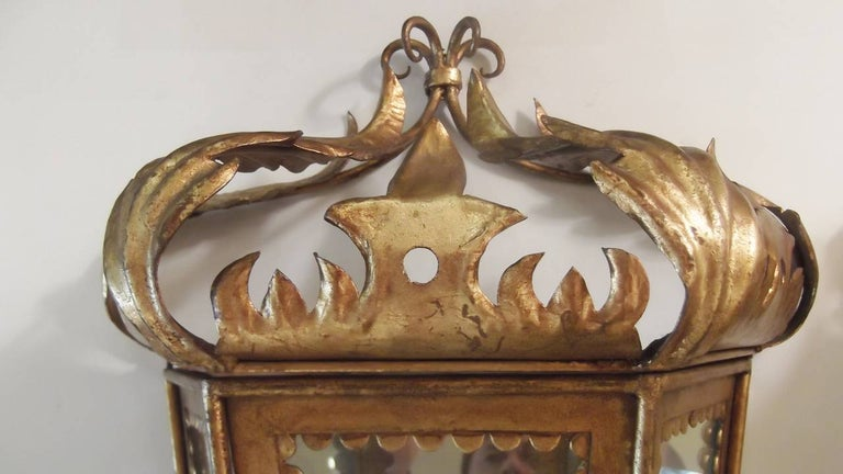 Whimsical Italian gilt toleware sconces with mirrored backs. Beautiful foliate design with glass panel front and sides. The top lifts off to assist with changing the bulb. Scalloped detail around the glass panels. These can be plugged in or have an