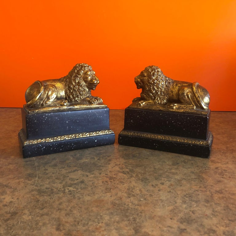Stunning pair of majestic lion bookends in a gold gilt finish on a faux black marble base by Borghese of Italy, circa 1960s. The pair is in great vintage condition and our made of cast plaster with a built in metal slide to go under the books. #1192.