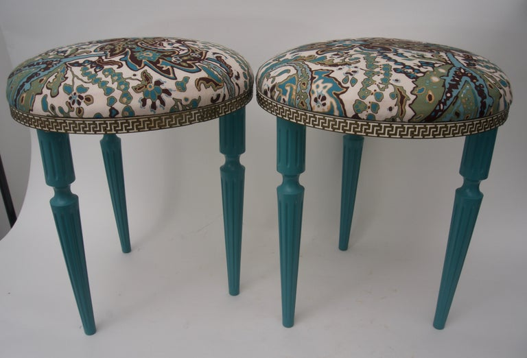 This stylish pair of stools are in the Hollywood Regency vain with there Louis XVI style frames that have been lacquered in a deep turquoise with a woven floral fabric seat which is bordered with a pierced metal band.