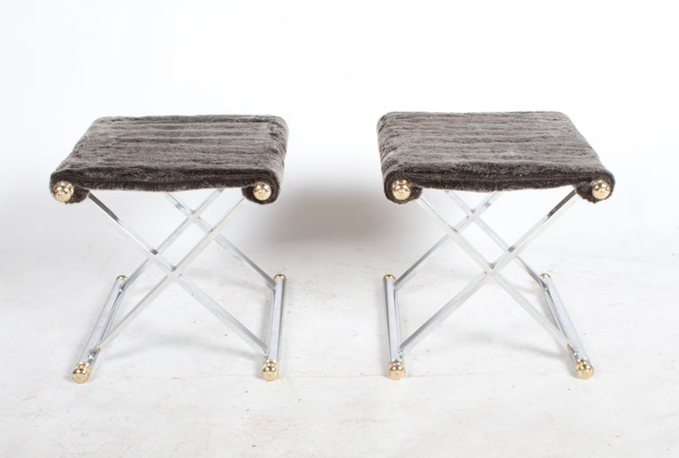 Pair of vintage Hollywood Regency X-base chrome and brass stools in the manner of Maison Jansen. The pair features polished chrome X-form frames, seamless joints, brass tone finials, with new faux beaver by Romo, color is silver tip seats. Chrome is