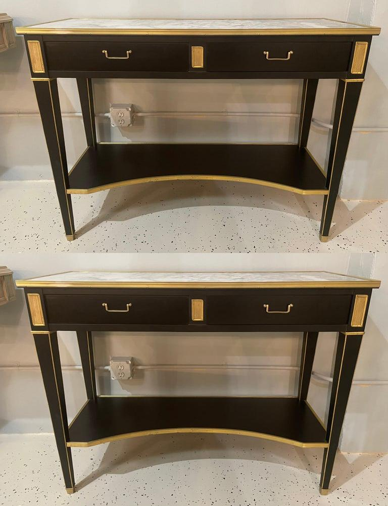 Pair of Hollywood Regency neoclassical ebony console or sofa tables in the manner of Maison Jansen. A stunning sleek and stylish pair of console tables in an ebony finish having a bronze framed marble top supported by a lower case of two drawers