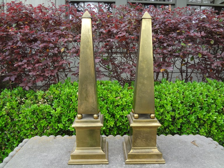 Great pair of Hollywood Regency brass obelisks. These beautiful midcentury Neoclassical style brass obelisks have a naturally occurring patina that could be polished if desired. Perfect table or bookcase accessory!