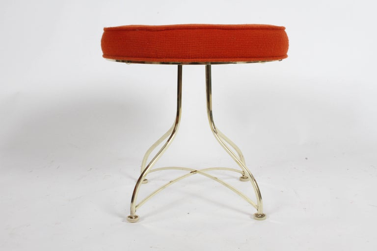 Pair of midcentury round stools or ottomans with tufted round seats and plated brass legs. Upholstery needs to be updated, shows stains. Brass plating has minor patina.