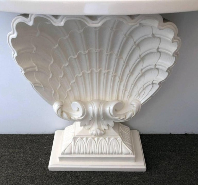 Pair of shell consoles having a cast plaster shell body, with a rounded front top and classical plinth base. These were purchased from two different estates. The colors might be slightly off. We can either have them re painted for you for a fee of
