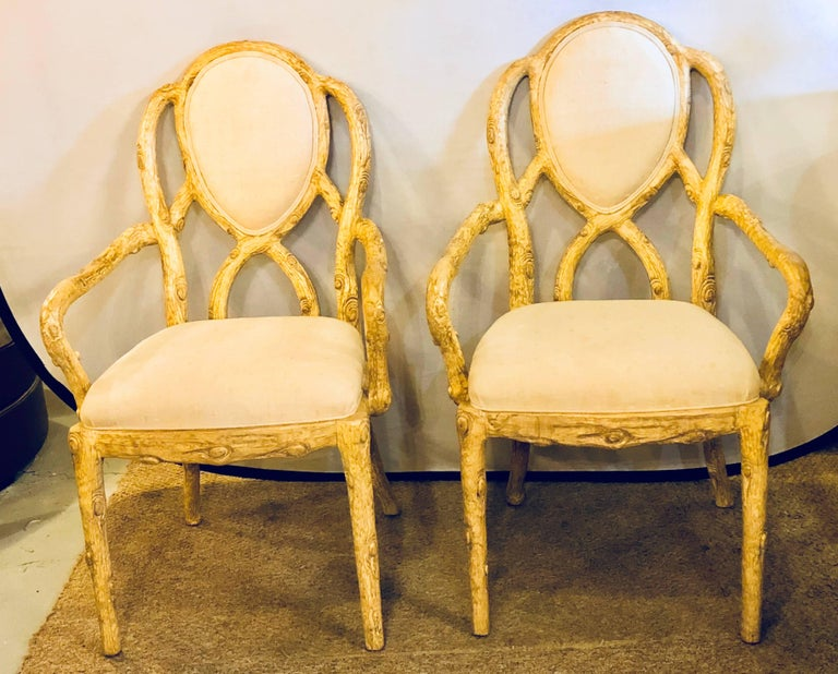 Pair of Hollywood Regency style tree trunk form designed armchairs. Each of these newly upholstered armchairs have been designed to look as though they were carved from a tree branch. The pair having comfortable sets and back rests with flowing