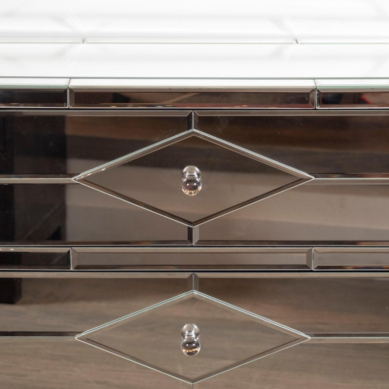 This pair of tessellated mirrored nightstands/end tables represent the bygone glamour and sophistication of the Hollywood Regency in stunning terms. Their bodies consist of a mosaic of geometric mirrored segments, creating subtle and dynamic