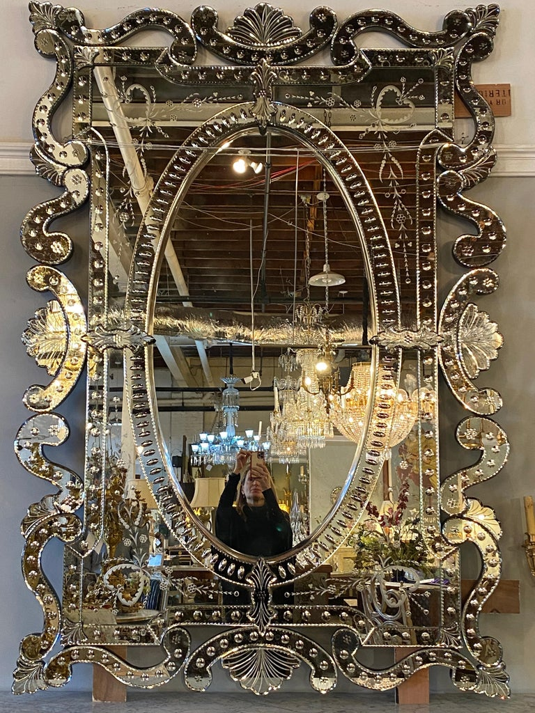 Hollywood Regency style pair of monumental hand etched and cut glass mirrors. These are simply the most impressive of wall or console mirrors. Large in size with finely cut single multiple pieces all formed together to make on impressive