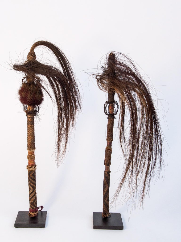 Pair of horsehair fly whisks. Yi of Yunnan, China, early to mid-20th century. Mounted on metal stands. Incorporating twining and braiding techniques.