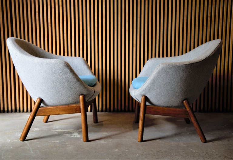Pair of pod chairs designed by Ib kofod Larsen and retailed by Povl Dinesen. The foam shells are newly upholstered in Light Gray and light blue contrasting Maharam Hallingdal wool fabric. The chairs float above refinished splayed turned oak legs. A