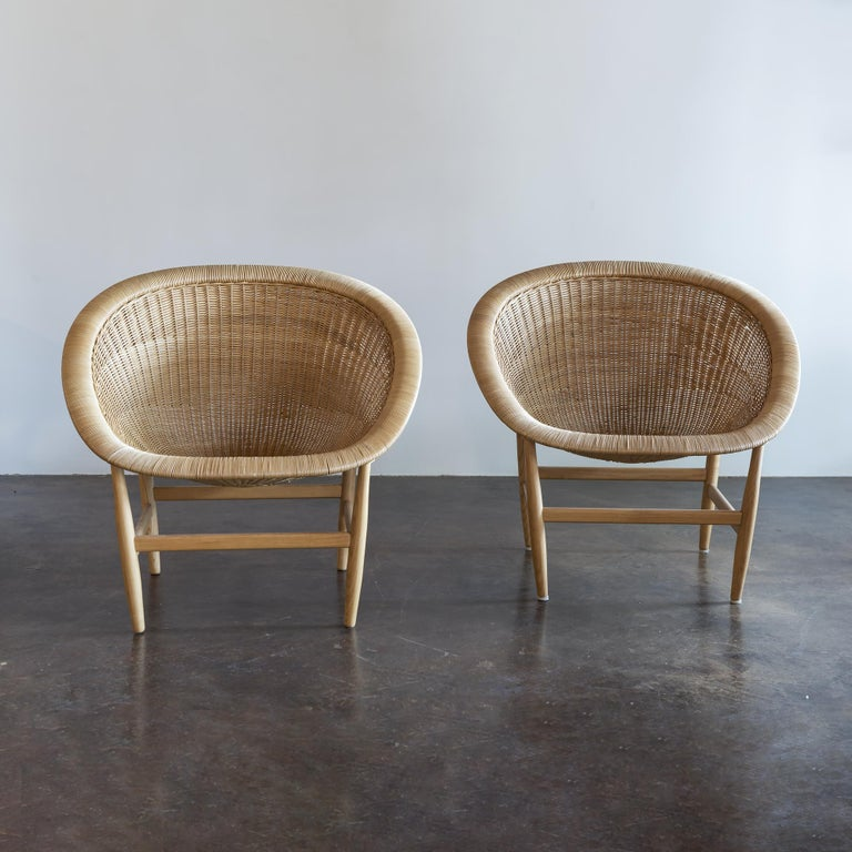 Iconic, organically shaped lounge chairs in hand-braided rattan and ash by Nanna Ditzel for Ludvig Pontoppidan, Denmark, 1950.  Pair of chairs comes with new cushions in Place Textiles Mt. Stuart fabric.