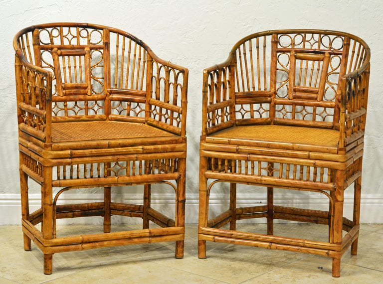 Rising on six legs this pair of intricately crafted iconic armchairs with cane seats feature bamboo frames and Chinese themed bamboo open work inspired by Chippendale design. They come with new cushions covered with Ralph Lauren Voyager fabric in