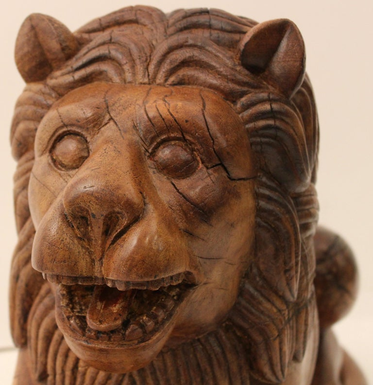 Pair of Indian carved teak recumbent lions architectural elements, circa 1900. Each lion with naturalistically modelled mane and features, its jaw open to reveal the tongue and teeth, modelled in a recumbent position with the tail curled around the
