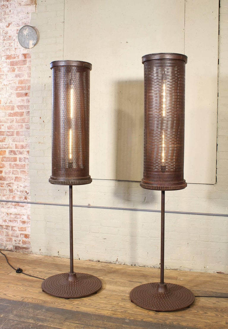 Pair of Industrial / Brutalist style 6' floor lamps. Turn of the century factory tumblers atop vintage steel machine bases. Features a foot switch and 40w Edison style tube bulbs. 72