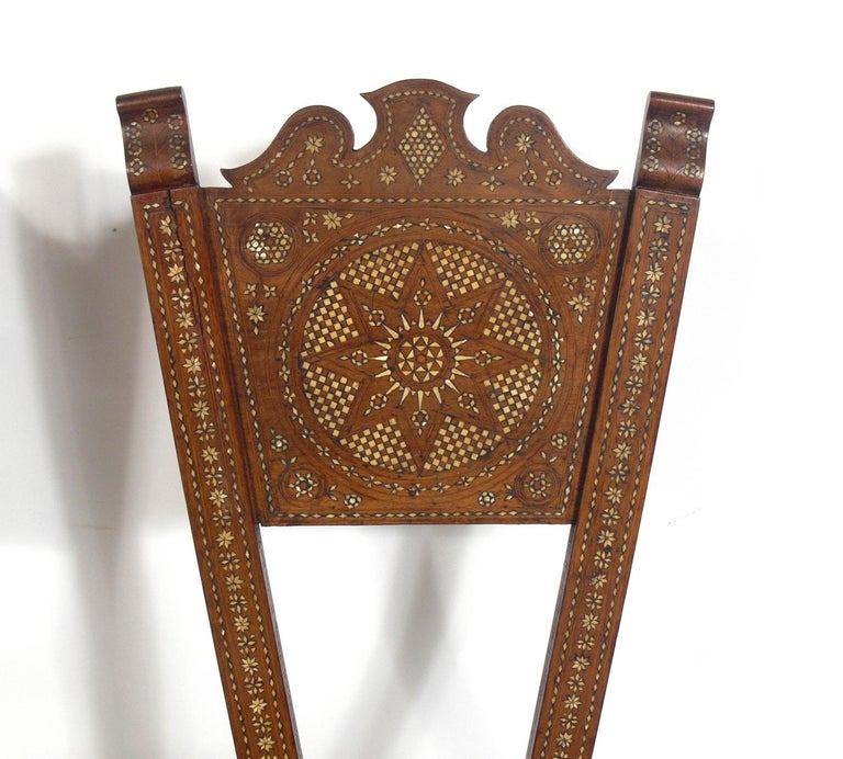 Inlaid Moroccan chair, in the manner of Carlo Bugatti, Moroccan, circa 1950s. They are completely handmade with intricate inlay throughout. They retain their warm original patina.