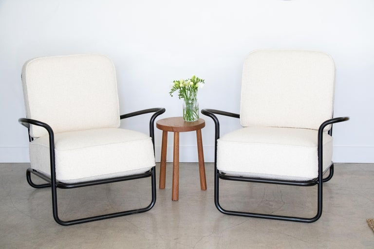 Pair of vintage black iron chairs with newly upholstered creamy boucle cushions. Matching square ottomans included.    Chair measures 34