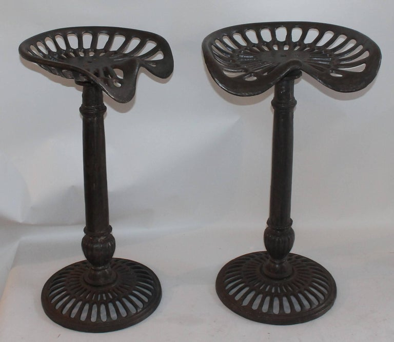 This pair of iron base and iron tractor seat bar stools are in good and sturdy condition.