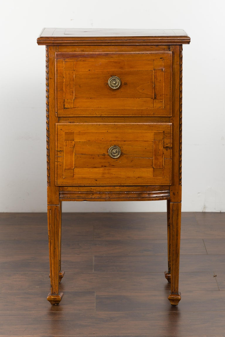 A pair of Italian neoclassical period walnut bedside tables from the early 19th century, with two drawers and tapered legs. Created in Italy during the first quarter of the 19th century, each of this pair of walnut bedside tables features a