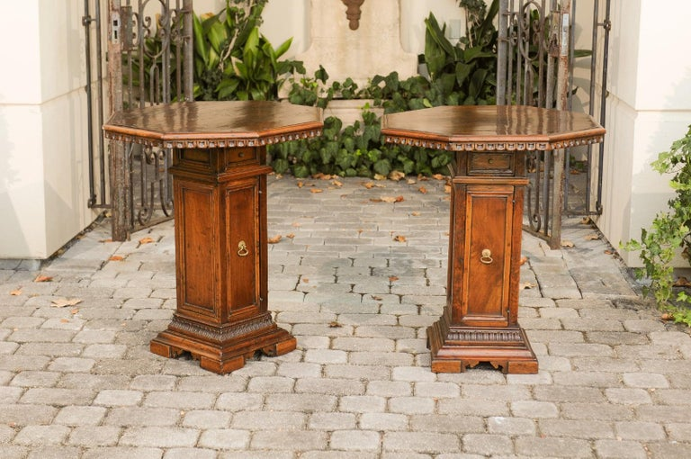 A pair of Italian octagonal walnut pedestal end tables from the mid-19th century, with single-door and drawer. Born in Italy during the mid-19th century, each of this pair of walnut tables features an octagonal top adorned with carved scoop patterns