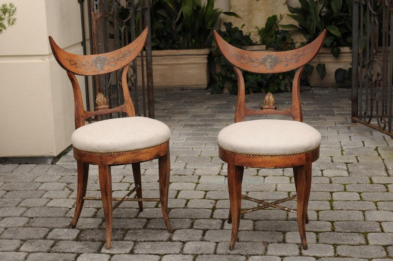 A pair of Italian side chairs from the mid-19th century, with crescent shaped backs, new linen upholstered seats and saber legs. Born in Italy during the third quarter of the 19th century, each of this pair of unusual Italian chairs features a