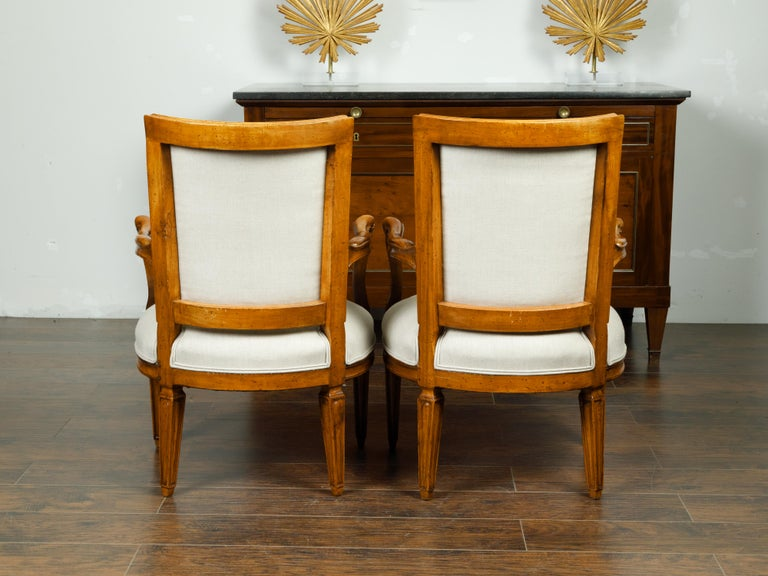 A pair of Italian walnut armchairs from the mid 19th century, with tapered legs and new upholstery. Created in Italy during the third quarter of the 19th century, each of this pair of walnut armchairs features a curving back connected to two sinuous